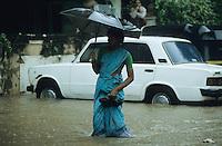 INDIA, Mumbai, Bombay, heavy monsoon rains flood the streets, woman in Sari with umbrella / INDIEN, Mumbai, schwere Monsun Regen ueberfluten die Strassen, Frau im Sari mit Regenschirm