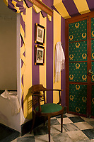 In a whimsical reference to the Battle of Trafalgar, the master bathroom of a Spanish town house has been furnished with Empire era furniture and details, while its walls have been painted to resemble battle tent drapery