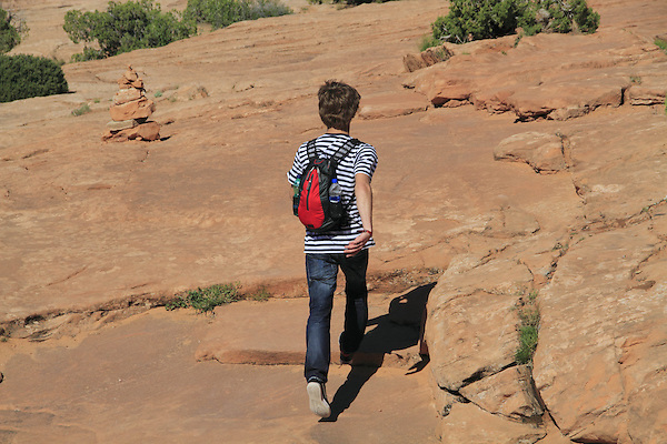 Boy running downhill on slickrock in Arches National Park, Moab, Utah, USA. .  John offers private photo tours in Arches National Park and throughout Utah and Colorado. Year-round.
