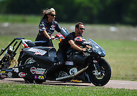 Apr. 28, 2012; Baytown, TX, USA: NHRA pro stock motorcycle rider Matt Smith is pushed back to the pits by wife Angie Smith during qualifying for the Spring Nationals at Royal Purple Raceway. Mandatory Credit: Mark J. Rebilas-