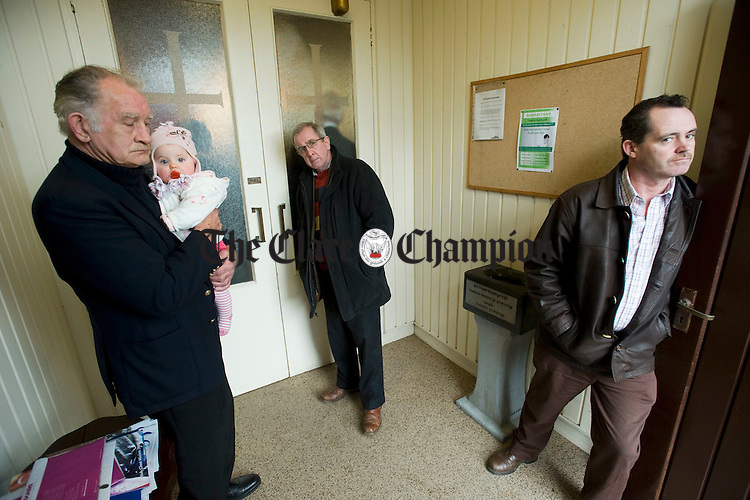 Martin Queally holds his grand niece baby Daire Griffin in the porch at the funeral of the late Joe Ryan in Inagh. Photograph by John Kelly.