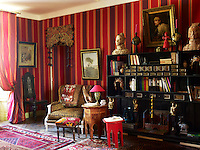 A guest bedroom features a 19th century portrait and Qin dynasty busts and the red side table is an heirloom from Gerard Tremolet's childhood