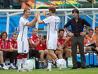 Thomas Muller of Germany is replaced by Lukas Podolski as Germany manager Joachim Low watches on