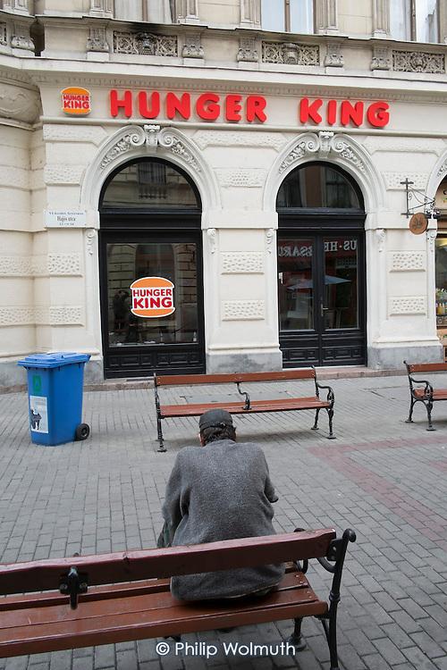 Homeless man on a bench opposite Hunger King, a restaurant modelled on Burger King, Budapest.