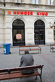 Homeless man on a bench opposite Hunger King, a restaurant modelled on Burger King, Budapest.