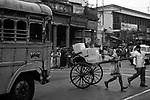 A rickshaw puller hurries through a traffic on a street in Kolkata, India