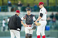 Great Lakes Loons pitcher Nolan Long (52) and catcher Brant Whiting (1) wait for pitching coach Bobby Cuellar (12) to meet on the mound against the South Bend Cubs on May 18, 2016 at Dow Diamond in Midland, Michigan. Great Lakes defeated South Bend 5-4. (Andrew Woolley/Four Seam Images)