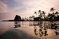 Sunset with reflections of palm trees in the water at Ahuena heiau, an ancient Hawaiian temple on the bay in Kailua-Kona