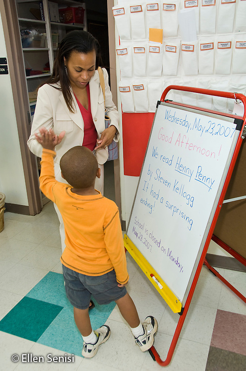 MR / College Park, Maryland.Center for Young Children, laboratory school within the College of Education at the University of Maryland. Full day developmental program of early childhood education for children of faculty, staff, and students at the university..Mother and son (4, African American) slap five in front of display board that tells what his class did in school that day. .MR: Wri4 Wri3.© Ellen B. Senisi