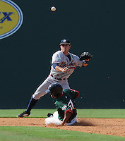 Infielder KC Clabough (5) of the Rome Braves turns a double play putting out Henry Ramos (51) of the Greenville Drive on July 8, 2012, at Fluor Field at the West End in Greenville, South Carolina. Clabough was a 28th-round pick of the Atlanta Braves in the 2012 First-Year Player Draft. Greenville won, 12-3. (Tom Priddy/Four Seam Images)