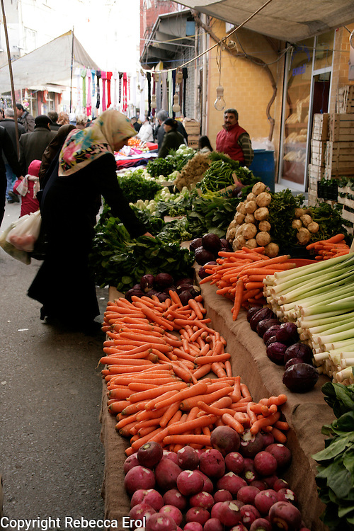Woman looking at vegetables for sale in a colourful market in Istanbul, Turkey