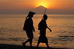 Fishermen on the beach while the sun sets behind Bali's Gunung Agung. Lombok, Indonesia, 2002