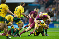Benn Robinson of Australia passes as he is tackled by Thomas Waldrom of England during the Cook Cup between England and Australia, part of the QBE International series, at Twickenham on Saturday 17th November 2012 (Photo by Rob Munro)
