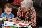 2 year old toddler boy at home with grandmother interaction read to from picture book vertical she takes care of him when parents work she takes care of him when parents work