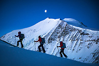 Ski touring in the pre-sunrise darkness using headlamps while on the way to the Brunegghorn, Switzerland