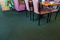 Pink and black chairs in restaurant diner with dirty green carpet.