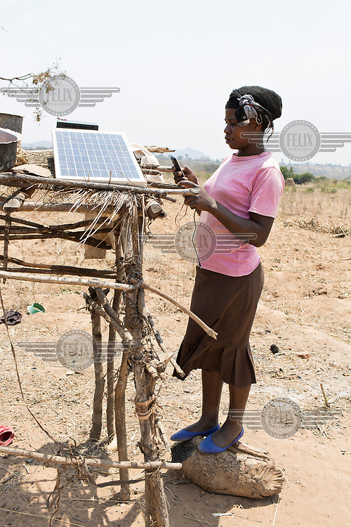 Isabel Mvula (34) checks a mobile phone which is charging from a solar power panel.