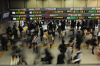 Passengers rush through the West Exit during morning rush hour, Shinjuku, Tokyo. With up to 4 million passengers passing through it every day, Shinjuku Station in Tokyo, Japan is the busiest train station in the world. The station was used by an average of 3.64 million people per day.  That's 1.3 billion a year.  Or a fifth of humanity. Shinjuku has 36 platforms, and connects 12 different subway and railway lines.  Morning rush hour is pandemonium with all trains 200% full. <br /> <br /> Photo by Richard jones / sinopix