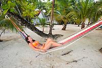 Honduras, Roatan Island, Fantasy Island Resort, Caribbean. Woman realxing in hammock at the beach (Sam).