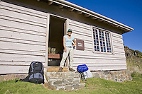 Asian-American woman standing outside Holua Cabin with backpack and sleeping bag, in the Haleakala crater