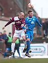 Arbroath's player / manager Paul Sheerin and Queen of the South's Chris Mitchell go for a high ball.
