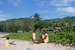 Family waiting for the sunset on one of the white sand  beach of La Digue.