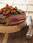 A large porterhouse steak on wooden cutting board with knife, topped with roasted red peppers and green olives