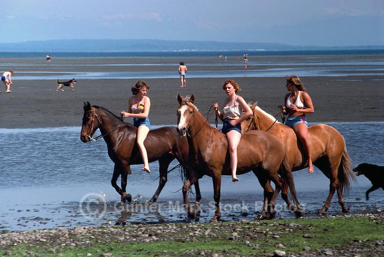 Teenage Girls horseback riding on Beach at Low Tide, along Pacific Ocean, BC, British Columbia, Canada