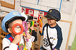 Education Preschool 3 year olds pretend play boy in dressup hat holding magnifying glasses to his eyes playing with another boy in dressup holding magnifying glass