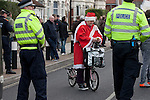 """Portsmouth 1 Southampton 1, 18/12/2012. Fratton Park, Championship. A woman on a bicycle dressed in a Father Christmas suit waiting to cross a line of police officers in a closed-off street outside Fratton Park stadium before Portsmouth take on local rivals Southampton in a Championship fixture. Around 3000 away fans were taken directly to the game in a fleet of buses in a police operation known as the """"coach bubble"""" to avoid the possibility of disorder between rival fans. The match ended in a one-all draw watched by a near capacity crowd of 19,879. Photo by Colin McPherson."""