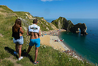 BNPS.co.uk (01202 558833)<br /> Pic: Graham Hunt/BNPS<br /> <br /> The coastguard helicopter lands on the beach at Durdle Door in Dorset to deal with a medical emergency on an afternoon of scorching hot sunshine and clear blue skies.<br /> <br /> A couple on the cliff top watch the scenes on the beach below where the crowd has been moved so the helicopter could land.