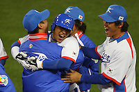 Jong Wook Lee of Korea is greeted by teammates during a game against Japan at the World Baseball Classic at Dodger Stadium on March 23, 2009 in Los Angeles, California. (Larry Goren/Four Seam Images)