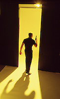 Man with gun on yellow seamless walking away from camera
