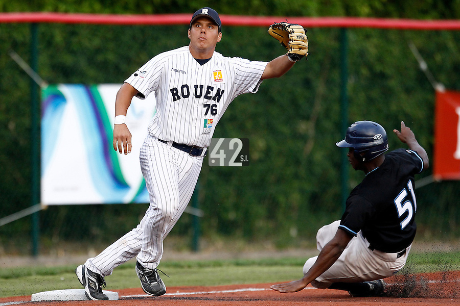 15 July 2011: Boris Marche of the Rouen Huskies eyes the ball as Jean Antonio Samer slides safely into third base during the 2011 Challenge de France match won 6-5 by the Rouen Huskies over the Senart Templiers at Stade Pierre Rolland, in Rouen, France.