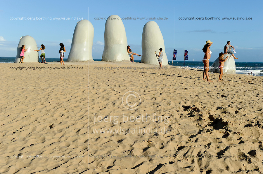 """URUGUAY Punta del Este, sculpture La mano ( The hand ) by Chilean artist Mario Irarrázabal. It depicts five human fingers partially emerging from sand, and is located on Parada 1 at Brava Beach. It is also known as either Hombre emergiendo a la vida (Man Emerging into Life), Monumento los Dedos (Monument of the Fingers) or Monumento al Ahogado (Monument to the Drowned) / URUGUAY Badeort und Seebad Punta del Este  """"Los Dedos"""" (die Finger), eine circa fünf Meter breite und drei Meter hohe Steinskulptur in Form einer Hand im Strandsand"""