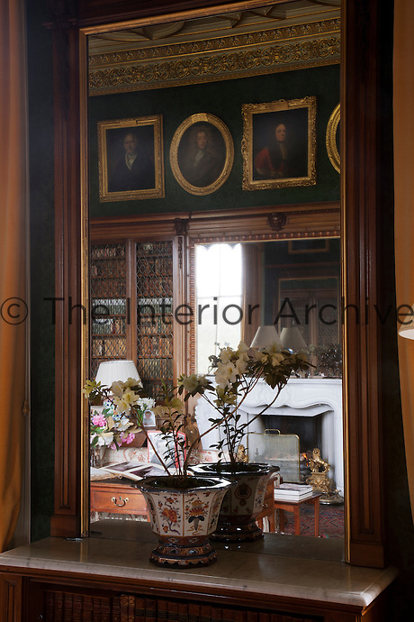 Reflection of the library fireplace and family portraits in the library