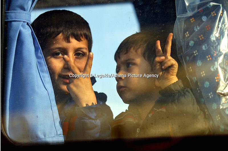 Pictured: Two young boys give the victory sign from a coach that transferred them to a local gymnasium Thursday 27 November 2014<br /> Re: One of the largest refugee boats in recent months has disembarked refugees in Ierapetra, Crete. The freighter Baris, carrying 700 people thought to be from Syria and Afghanistan, is being towed by a Greek frigate.<br /> Officials and Red Cross volunteers prepared an indoor basketball stadium as interim shelter in the southern Cretan port town of Ierapetra on Wednesday ahead of the migrants' expected arrival.<br /> Greek officials said the Baris, which lost propulsion on Tuesday, was being towed slowly in poor sea conditions and would arrive after nightfall, probably early Thursday.<br /> They said it was unclear which Mediterranean location had been the departure point for the 77-meter (254-foot) vessel, which was sailing under the flag of the Pacific nation of Kiribati.