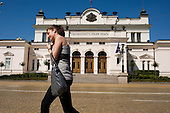 A young woman with a mobile phone passes the Bulgarian National Assembly, Sofia.  The inscription reads 'Unity is Strength'