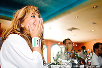 Iran fan Farideh anxiously watches the Iran-Mexico World Cup match at the Persian Tea Room in the New York City area on June 11, 2006.<br /> <br /> The World Cup, held every four years in different locales, is the world's pre-eminent sports tournament in the world's most popular sport, soccer (or football, as most of the world calls it).  Qualification for the World Cup is open to any country with a national team accredited by FIFA, world soccer's governing body. The first World Cup, organized by FIFA in response to the popularity of the first Olympic Games' soccer tournaments, was held in 1930 in Uruguay and was participated in by 13 nations.    <br /> <br /> As of 2010 there are 208 such teams.  The final field of the World Cup is narrowed down to 32 national teams in the three years preceding the tournament, with each region of the world allotted a specific number of spots.  <br /> <br /> The World Cup is the most widely regularly watched event in the world, with soccer teams being a source of national pride.  In most nations, the whole country is at a standstill when their team is playing in the tournament, everyone's eyes glued to their televisions or their ears to the radio, to see if their team will prevail.  While the United States in general is a conspicuous exception to the grip of World Cup fever there is one city that is a rather large exception to that rule.  In New York City, the most diverse city in a nation of immigrants, the melting pot that is America is on full display as fans of all nations gather in all possible venues to watch their teams and celebrate where they have come from.