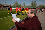 A spectator reading the match programme as the visitors warm-up before Ilkeston Town host Walsall Wood in a Midland Football League premier division match at the New Manor Ground, Ilkeston. The home team were formed in 2017 taking the place of Ilkeston FC which had been wound up earlier that year. Watched by a crowd of 1587, their highest of the season, the match was top versus second, however, the visitors won 4-0 and replaced their hosts at the top of the division on goal difference with two matches to play