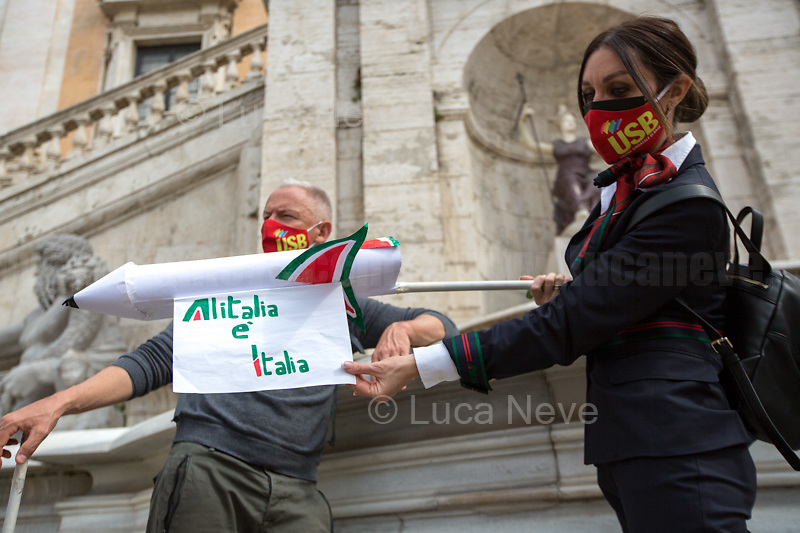 Rome, Italy. 16th Apr, 2021. Today, Alitalia, air transport, Airports, logistic, and related workers, led by CGIL, CISL, UIL, USB, CUB Trasporti Trade Unions, held a protest which started in Via dei Fori Imperiali against the plan under discussion between Mario Draghi's Italian Government and the European Union (EU - UE) to dismantle the flag carrier of Italy, make it a small and regional airline with a different name - while it is still one of the biggest airport slots owner in the world -, and to lay-off the majority of the workers of the Italian historical air company. During the demo, a group of protesters, patrolled by a conspicuous number of police officers, were allowed to demonstrate outside Campidoglio, the Rome's City Hall.   <br /> <br /> Footnotes & Links:<br /> Previous Demo: 03.03.2021 - Alitalia Workers Protest Outside Italian Ministry Of Transport https://lucaneve.photoshelter.com/gallery/03-03-2021-Alitalia-Workers-Protest-Outside-Italian-Ministry-Of-Transport/G0000JI_TNBKDjz8/C0000GPpTqAGd2Gg