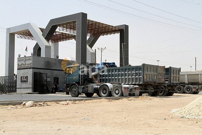 Trucks stand near the gate under Palestinian control at the Kerem Shalom crossing between Israel and the southern Gaza Strip, south of Rafah on June 7, 2015 after Israel closed, until further notice, the Erez crossing for people and the Kerem Shalom crossing for goods as Gaza militants resumed their rocket fire on southern Israel after warplanes blitzed the coastal enclave. Photo by Abed Rahim Khatib