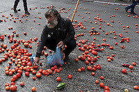 Pictured: A man collects tomatoes from the road after having been thrown by protesters to the police Friday 12 February 2016<br />