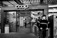 "Switzerland. Canton Ticino. Lugano. Supermarket Coop. A security guard working for the private company Securitas stands at the entrance of Coop Supermarket. The man wears a mask on the face and gloves on his hands to protect himself from the Coronavirus (also called Covid-19). His job is to control the door and and let enter only a restricted number of customers. Due to the spread of the coronavirus, the Federal Council has categorised the situation in the country as ""extraordinary"". It has issued a recommendation to all citizens to stay at home, especially the sick and the elderly. The Federal Council (German: Bundesrat, French: Conseil fédéral, Italian: Consiglio federale, Romansh: Cussegl federal) is the seven-member executive council that constitutes the federal government of the Swiss Confederation. From March 16 the government ramped up its response to the widening pandemic, ordering the closure of bars, restaurants, sports facilities and cultural spaces. Only businesses providing essential goods to the population – such as grocery stores, bakeries and pharmacies – are to remain open. The Swiss Securitas Group stands for the optimal combination of technical security and safety solutions and services. It is the best partner for companies wishing to make everyday life safer. Coop is one of Switzerland's largest retail and wholesale companies. It is structured in the form of a cooperative society with around 2.5 million members. 18.03.2020 © 2020 Didier Ruef"