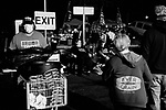 MIDDLETOWN, PA — SEPTEMBER 26, 2020:  Supporters of President Donald Trump watch the rally from the parking lot during the Covid-19 pandemic at the Harrisburg International Airport on September 25, 2020 in Middletown, PA.  Thousands of attendees, most of whom were maskless, rode on shuttle busses to and from the long term parking lot and the event site— as the world nears one million Covid-19 deaths— defying the states ban on gatherings over 250 people.  Photograph by Michael Nagle
