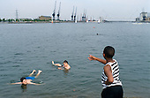 Boys swim in the Royal Victoria Dock, Newham, which will be a watersports venue for the 2012 Olympic Games, if London's bid is successful.