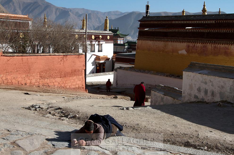 A Tibetan woman prostrates at Labrang (Chinese Name - Xiahe) Monastery on the Qinghai-Tibetan Plateau. China.