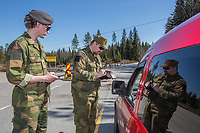 Home Guard soldier Thore Rinden making notes, with Kristian Moen looking on. Norwegian authorites introduced strict measures to combat the Coronavirus (COVID-19) in March 2020. This included closing the borders, and any Norwegians returning from abroad is given two weeks quarantine. <br /> <br /> Police and soldiers from the Home Guard of the Army (Heimevernet) man checkpoints along side roads and regular border crossings to enforce the travel restrictions.<br /> <br /> <br /> <br /> ©Fredrik Naumann/Felix Features