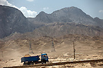 5 June 2013, Kholm District Hospital, Mazar-i-Sharif, Balkh Province, Afghanistan. Heavy vehicles woring the area in Kholm District outside Mazar-i-Sharif in front of a spectacular backdrop of mountains . Picture by Graham Crouch/World Bank.