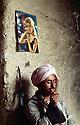 Iraq 1963 .A peshmerga in an house smoking and above him a poster of Brigitte Bardot.Irak 1963.Un peshmerga allumant sa cigarette dans une maison, avec au-dessus de lui le portarit de Brigitte Bardot